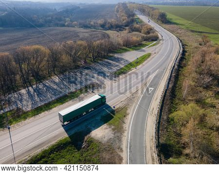 Moscow , Russia - SPT 23, 2020:   White Truck with Cargo Semi Trailer Moving on Road in Direction. Highway intersection junction  Aerial Top View