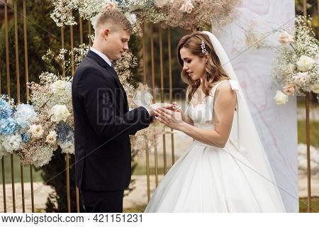 Young Couple Wedding Ceremony. Bride And Groom Exchange Wedding Rings, Put On A Finger.young Bride P