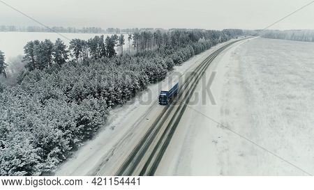 Aerial View Of A B Freight Truck Driving Down A Highway Running Along A Railroad On A Clear Winter D