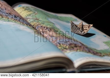 Paper Boat On The Atlas Of The World. The Open Book. Creative Image.