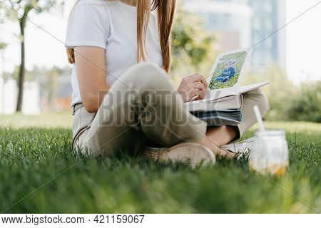 Top View Of Cropped Woman Hands Holding And Watching A Family Photo Album. Mother Sit On Green Grass