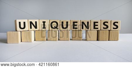 Inclusiveness And Uniqueness Symbol. Wooden Cubes With The Word 'uniqueness'. Beautiful White Backgr