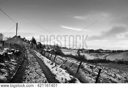 Monochrome View Of A Snow Covered Narrow Country Lane With A Row Of Stone Houses Surrounded By Field