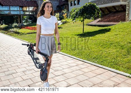 Pretty Young Woman Carrying Her Folded Electric Scooter As She Gets Ready To Take A Ride