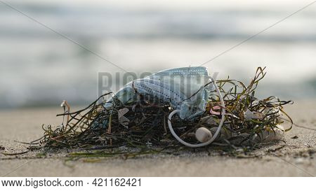 Close Up View Of Used Protective Face Mask Discarded On Marine Ecosystem, Medical Covid19 Pollution