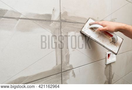 Grouting ceramic tiles. Tilers filling the space between tiles using a rubber trowel