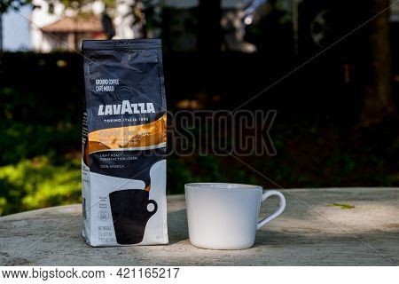 Coffee cup with bag Lavazza coffee outside