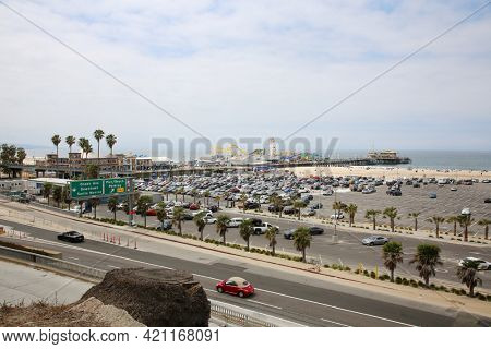 May 14, 2021 Santa Monica California, USA: Santa Monica Pier and Parking Lot filled with cars. People are enjoying a day on the Santa Monica Pier outside. Editorial Use.