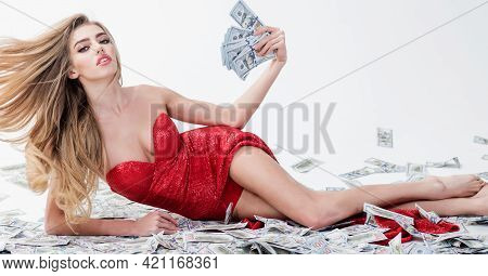 Successful Businesswoman Lying In Banknotes. Beautiful Girl In Elegant Red Dress Holds Money In Hand