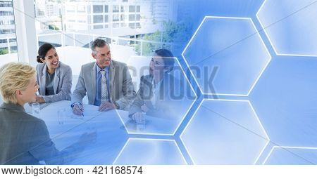Composition of smiling male and female business colleagues with blue hexagon overlay. global business, partnership and success concept digitally generated image.