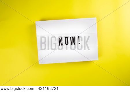 Lightbox With Message Now Isolated On Yellow Background. Concept Of Motivation, Hurry Up Sale Announ