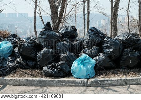 A Large Pile Of Black Garbage Bags. Garbage Removal On The City Streets. Seasonal Cleaning Of City S