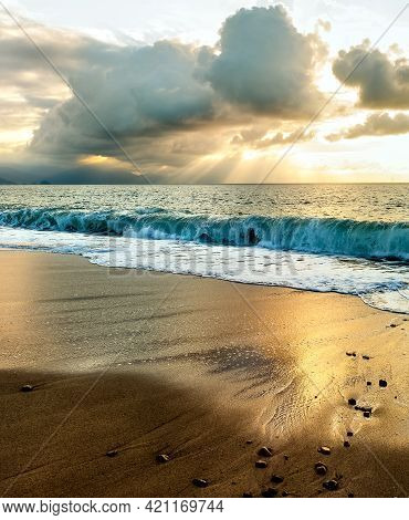 Sun Rays Break Through The Clouds As The Sun Sets On The Ocean Horizon In A Vertical Image Format