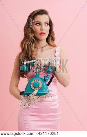 Young woman barbie in pink dress calling on landline phone over isolated background
