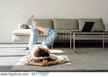 Young curly woman listening music with headphones while lying on floor at home