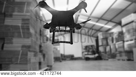 Drone flying over a warehouse in black and white, delivery and technology concepts. digitally generated image