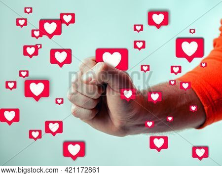 A man grabs with his hand the likes on social networks and squeezes one icon into his fist, successful blogging and youth culture concept. Fame and universal acceptance on the Internet