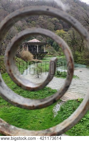 An Abandoned Pavilion At The Psyrtskha Railway Station. Abkhazia. View Through The Lattice Of The Pe