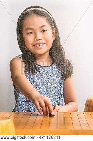 Portrait Asian Child Girl Is Playing Go With The First Move Of Black Stone. The Chinese Board Game O