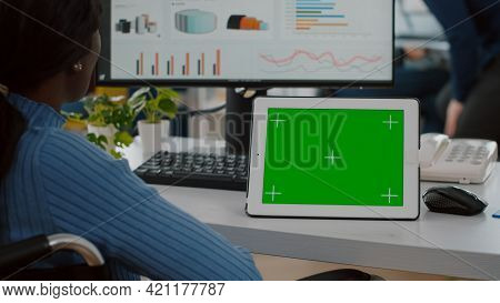 Immobilized African Businesswoman In Wheelchair Looking At Digital Tablet With Green Screen Chroma K