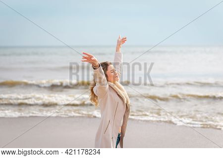 Relaxed Woman, Arms Rised, Enjoying Spring Sun, On A Beautiful Beach. Young Lady Feeling Free, Relax