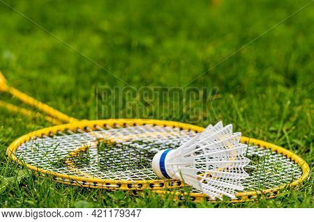 White Shuttlecock On Yellow Badminton Rackets In The Green Meadow