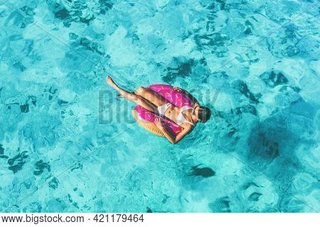 Beach vacation woman relaxing in pool float donut inflatable ring floating on turquoise ocean water background in Caribbean travel summer. Girl in white bikini top drone view.