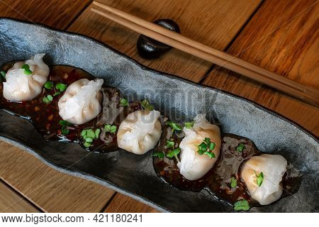 Top View Of Dimsum With Shrimp And Bamboo. Steamed Dumplings On Black Plate. Wooden Background. Trad