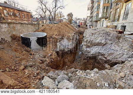 Deep And Long Trench Dug Out In Ground Near A Modern New Building Under Construction. Street With Ol