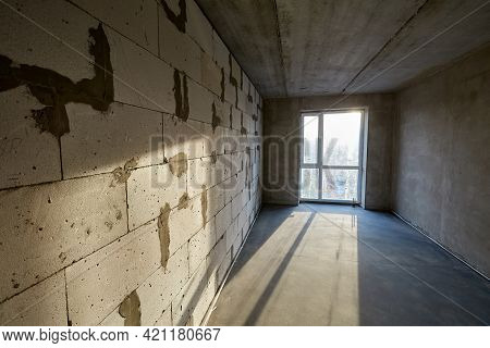 Unfinished Empty Room With Plastic Window, Walls Made Of Aerated Concrete Blocks And Cement Screed O