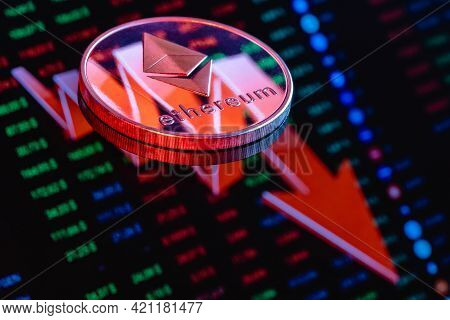 Ethereum Coin On The Background Of A Large Red Arrow Pointing Down. The Concept Of The Falling Rate