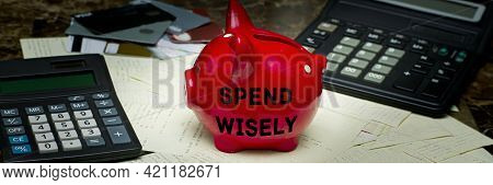 Spend Wisely Text On A Piggy Bank Standing On Cashier's Checks From Shops Near Calculators And Credi