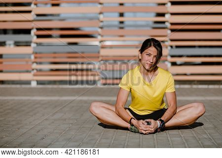 Portrait Of Fit And Sporty Young Woman Doing Stretching In City. Young Fitness Woman Runner Stretchi