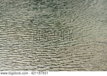 Texture Of Golden Turquoise Calm Water Of Lake. Meditative Ripples On Water Surface. Nature Minimal