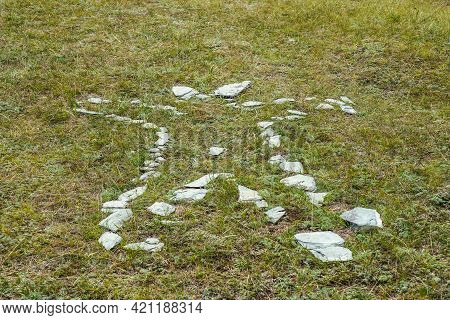 White Stones Laid Out On Green Grass In Man Shaped. Art Nature Background With Stones On Ground In S