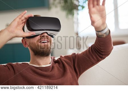 Young Bearded Guy Sitting On Sofa And Exploring Virtual Reality With Headset Raising Arms And Immers