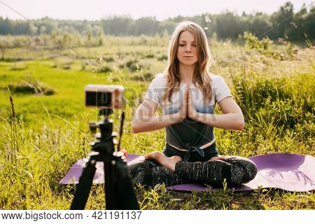 The Girl Practices Yoga In Nature And Records A Video Lesson About Yoga. Yoga Online, Training Onlin