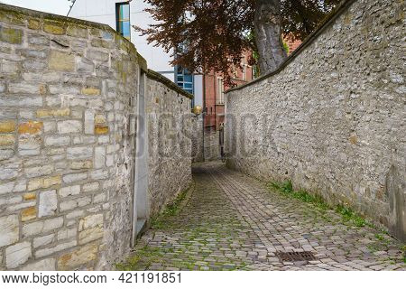 Narrow Passage To A Residential Building Between Two Stone Walls. The Sidewalk Is Lined With Paving