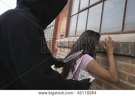 Junge weibliche Räuber erschrecken eine Frau mit Messer und raubt Geld von ihr