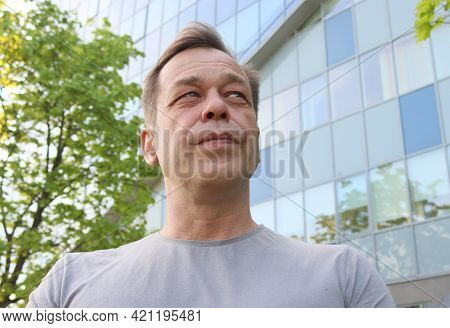 Street Portrait Of A Man 40-50 Years Old In A Gray T-shirt Against The Background Of A Business Cent