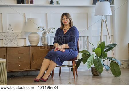 Extravagant Dressy Lady At Home. Portrait Of A Confident Mature Woman. Smiling Woman Looking At Came