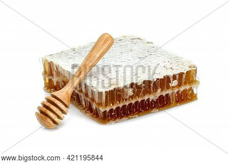 Fresh Honeycomb Slice And Wooden Honey Dipper Isolated On White Background