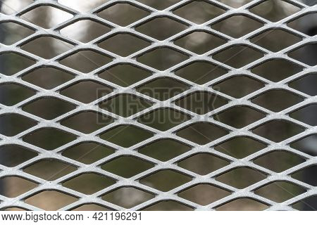 Metal Mesh Grid In Weathered Stained Steel. Close Up.