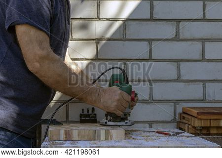 A Carpenter At A Hand-held Hand-held Milling Machine In A Carpentry Workshop. End Cutting Boards. Jo