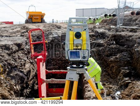 Yellow Equipment Set Out On Tripod On Building Site Against Cloudless Blue Sky. Construction Site Su