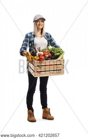 Full length portrait of a young woman farmer carrying a crate with vegetables and smiling isolated on white background