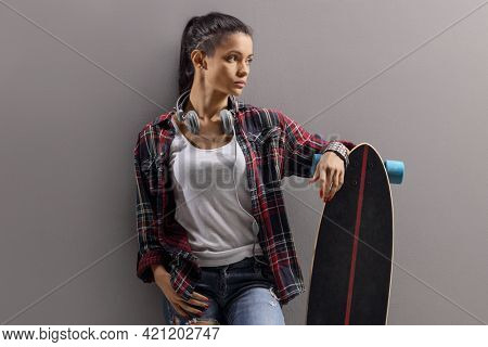 Trendy young female with a longboard leaning on a grey wall