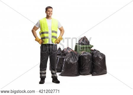 Full length portrait of a waste collector standing in front of bin bags isolated on white background