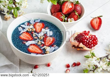 Butterfly Pea Flower Chia Pudding With Strawberries, Pomegranate And Granola In A White Bowl On A Wh