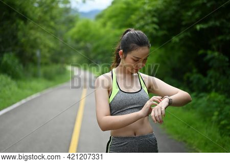 Attractive Running Female Checking Her Smart Watch With Static Step Data.